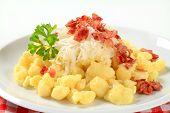 Hot little potato dumplings with bacon and sauerkraut on a plate