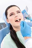 Dentist is looking for the defects in the oral cavity of the patient on the dentist's chair