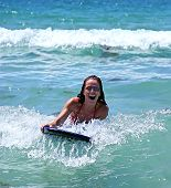 Girl Smiling While Riding A Big Blue Wave On A Body Board On The Blue Sea On A Sunny Day.