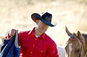 picture of buckaroo  - Cowboy in red shirt and his horse out working in early morning light - JPG