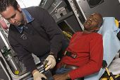 Male EMT professional taking care of a middle aged man inside ambulance