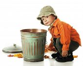 An adorable preschooler picking up colorful leaves to put in a small trash can.  On a white backgrou