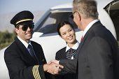 Senior Businessman Händeschütteln mit einem Flugzeug-Kapitän und Stewardess mit Airfie im Hintergrund