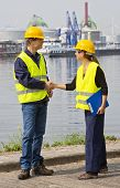 Two dockers, a man and a woman shaking hands in an industrial harbor, wearing the necessary safety g
