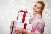 Smiling woman in cashmere sweater with gift boxes