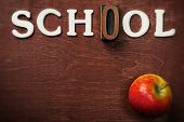 The word school written on wooden background