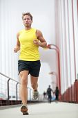 Fit runner running outside. Young male fitness model training in yellow on Golden Gate Bridge, San F