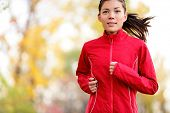 Woman runner running in autumn forest. Young mixed race girl jogging in fall colors.
