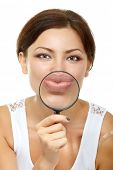 Smiling attractive give kiss through a magnifying glass over white background