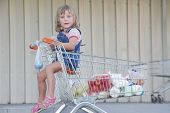 young girl with shopping basket in supermarket