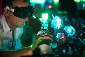 Scientist  in laser vision glasses engaged in research in his lab show movement of microparticles by