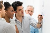 stock photo of chart  - Group Of Business People Analyzing Graphs and Charts in Office - JPG
