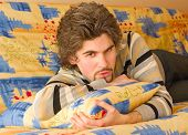 Young Serious Handsome Male On Colourful Sofa