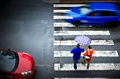 stock photo of street-walker  - pedestrian crossing with car in the rain - JPG