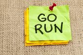 go run reminder or fitness concept - handwriting on green sticky note