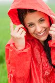 Portrait of cheerful teenager in the rain in red raincoat