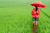Smiling young woman standing on meadow on rainy day