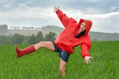 stock photo of dancing rain  - Playful teenage girl dancing in the rain on a field - JPG