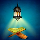 Hanging illuminated arabic lamp and open holy book Quran on blue background for Ramadan Kareem.