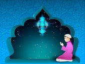 Ramadan Kareem background with a Muslim boy in traditional dress praying.