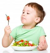 Cute little boy eats vegetable salad using fork, isolated over white