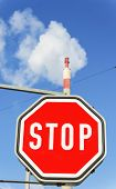 chimney of an industrial company and stop sign. symbolic photo for environmental protection and ozon