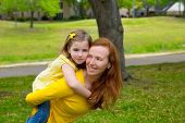 Daughter and mother piggyback smiling happy in park outdoor