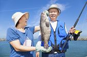 pic of grouper  - happy asian senior couple fishing and showing big grouper - JPG