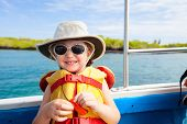 stock photo of life-boat  - Adorable little girl in a life jacket traveling on boat - JPG