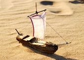 Wooden Sail Ship Toy Model In The Sea Sand
