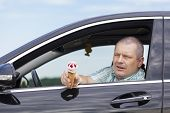 Man sitting in a car offers ice cream