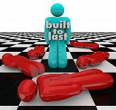 A person or man on a chessboard with the words Build to Last among other poeple who have fallen or d