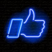 Neon Thumbs Up symbol on brick wall background