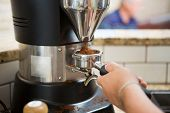 Cropped image of barista grinding fresh coffee into bayonet