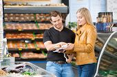 stock photo of deli  - Caucasian couple checking ingredients of product at butcher - JPG