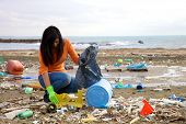 stock photo of polluted  - Young activist volunteering on the beach after ecological disaster - JPG