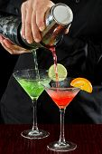 stock photo of bartender  - professional bartender pouring two martinis at the same time in a fluid motion - JPG