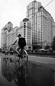Young Boy Ride Bicycle With High-rise Building Background