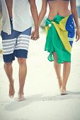 Couple in love walking on beach with Brazil flag sarong