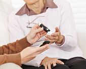 Blood sugar measurement in hand for senior citizen woman