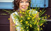 Smiling woman has a nice time behind a bunch of self-picked buttercups