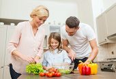 food, family, hapiness and people concept - happy family making dinner in kitchen