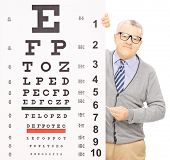 Senior man standing behind eyesight test and pointing with a wooden stick, isolated on white background, shot with a tilt and shift lens