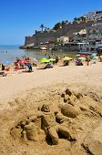 PENISCOLA, SPAIN - JULY, 26: Sand sculpture and bathers in North Beach, facing the castle, on July 2