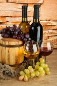 composition of wine and grapes on wooden barrel on table on brick wall background