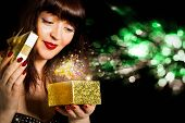 Beautiful Girl opens a gift in a small box golden