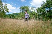 foto of lederhosen  - Young man in traditional Bavarian lederhosen walking alone in the field - JPG