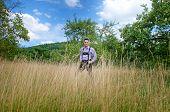 pic of lederhosen  - Young man in traditional Bavarian lederhosen walking alone in the field - JPG