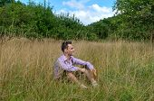 Young man in traditional Bavarian lederhosen relaxing in the field