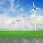 Wind Mill Power Plant In Green Field And Wood Plant Against Blue Sky